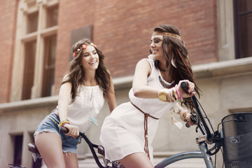 Retro portrait of two friends riding tandem bicycle