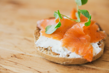 Salmon tartine on rustic wooden background with shallow dof