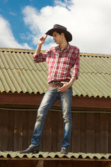 Young romantic cowboy is on the roof
