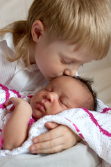 Multiracial family concept. Brother kissing newborn