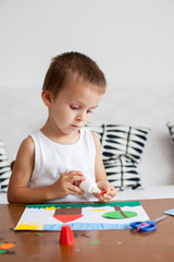 Adorable boy, making decoration picture from colorful paper