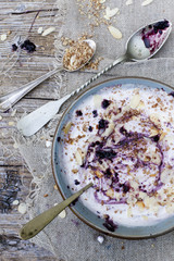 white yogurt with blackberries muesli and almond slices on bowl