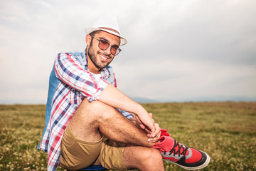 relaxed casual man sitting on a chair in a field