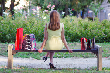 Elegant lady sitting in the park after shopping
