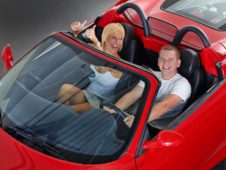 Young couple has fun to drive a red roadster