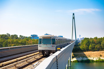 Vienna metro train passing a bridge over Danube river