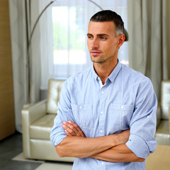 Portrait of a pensive man with arms folded at home