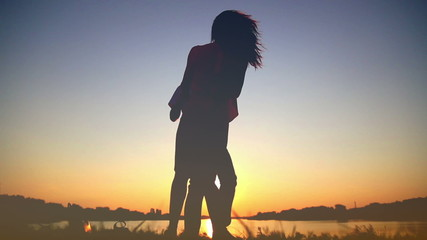 Young couple in love at sunset on the lake, enjoying each other,