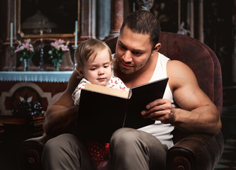 Father reading book to daughter