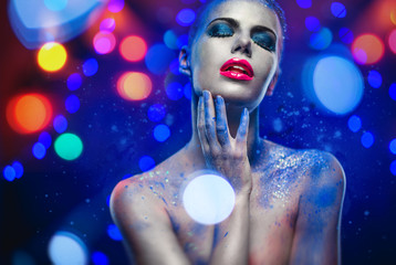 Woman with creative make-up over glowing lights