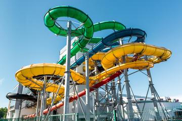 Tube slides at water park against blue sky