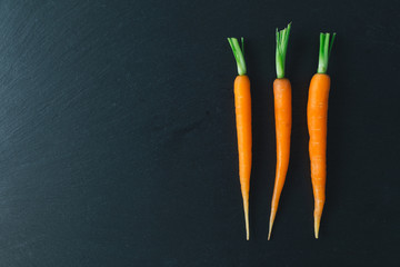 Top view of baby carrots on black slate background