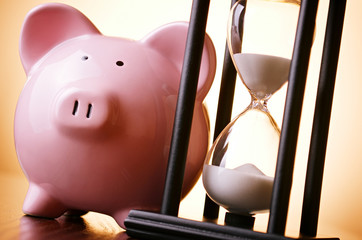Pink piggy bank with a vintage hourglass behind