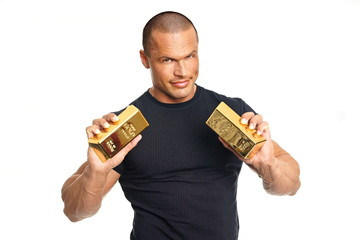 Muscular man in black shirt shows you gold brick