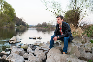 junger mann sitzt am fluss