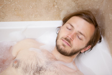Man lying in a bubble bath tube relaxing.