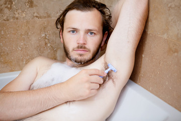 Man lying in a bath tube shaving his armpit