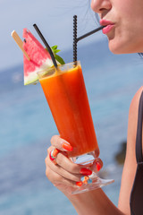 Woman with cocktail glass near sea. Blurred sea on background.
