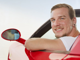 Man driving a red roadster