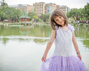 Little girl in dress standing in front of a lake
