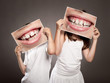 two children holding a picture of a mouth smiling - 68074497