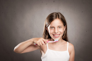 girl brushing her teeth on a gray background