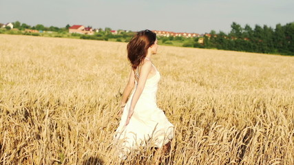 Young woman running through wheat field