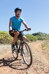 Fit cyclist riding on country trail