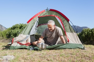 Happy camper cooking on camping stove outside his tent