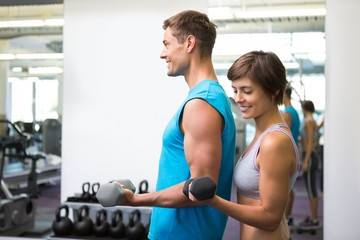 Fit happy couple lifting dumbbells together