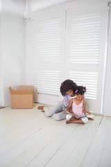 Mother and daughter sitting on the floor reading storybook