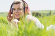 Pretty blonde lying on grass listening to music