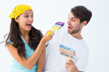 Happy young couple painting together and laughing