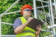 Worker with folder near the fence