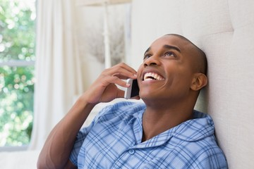 Happy man sitting on bed and talking on phone