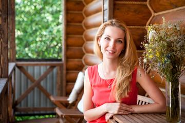Красивая девушка в красном платье сидит возле деревянного домика
