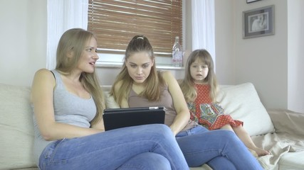 Two women and little girl sitting on couch with tablet computer