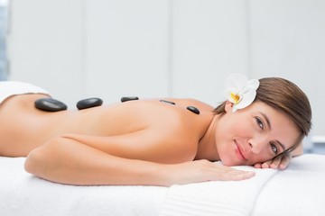 Beautiful woman receiving stone massage at spa center