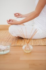Peaceful woman sitting in lotus pose on bamboo mat