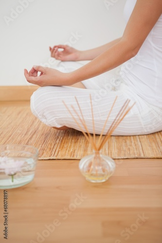canvas print picture Peaceful woman sitting in lotus pose on bamboo mat