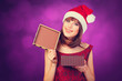 Girl in xmas hat with gift box on violet background.