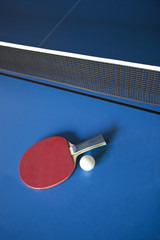 Racket and ball on a ping pong table
