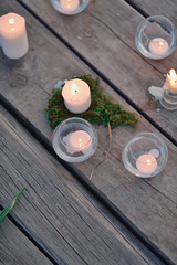 the river on a wooden bridge burning candles in glass candlestic