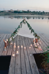 the river on a wooden bridge white tent and burning candles