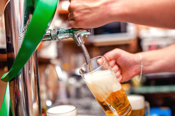 close-up of barman brewing a draft beer at pub
