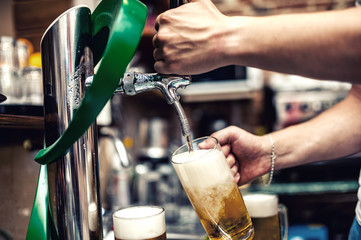 Barman pouring or brewing a draught beer at restaurant, bar