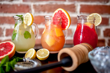 lemonades with ingredients in bar on counter or wooden table