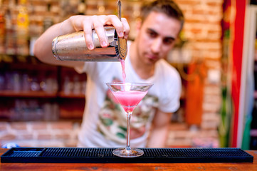 bartender preparing and pouring cosmopolitan alcoholic cocktail