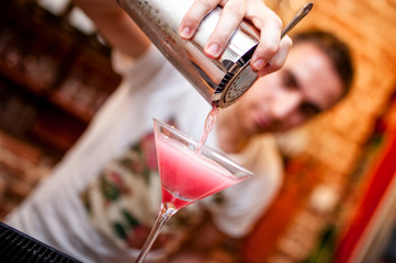 barman preparing and pouring cosmopolitan alcoholic cocktail