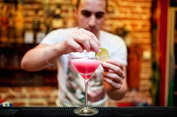 barman preparing cosmopolitan alcoholic cocktail drink at bar